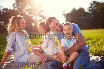 Молодая семья с детьми веселятся на природе.