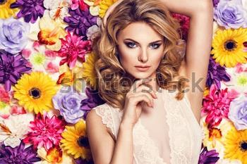 Красивая чувственная женщина в кружевном белье на фоне стены с цветами. Красивые волосы. Фото на тему красоты.