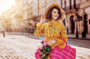 Уличный портрет молодой красивой счастливой девушки, носящей желтое платье в горошек, шляпу, держа соломенную сумку с пионами. Девушка стоит на улице европейского города. Весна, летняя мода.