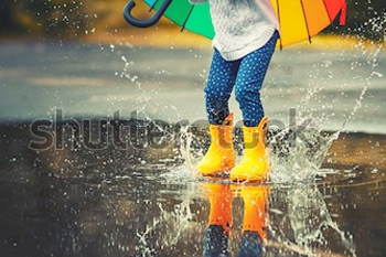 Ноги ребенка в желтых резиновых сапогах прыгают через лужу под дождем